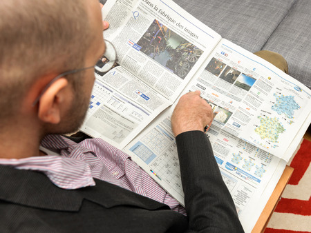 programmes: PARIS, FRANCE - NOV 12, 2016: Man reading Le Figaro et Vous lifestyle French newspaper  - reading TV Programme for the next week, pointing to Canal +