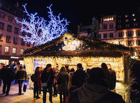 christkindlesmarkt: STRASBOURG, FRANCE - NOV 28, 2015: Traditional Christmas Market chalet in Strasbourg Alsace France with people shopping gifts,toys and presents