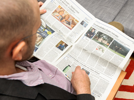 newsfeed: PARIS, FRANCE - NOV 12, 2016: Man reading Le Figaro et Vous lifestyle French newspaper - article about pensions