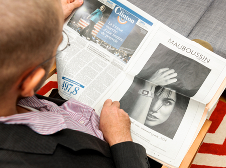 newsfeed: PARIS, FRANCE - NOV 12, 2016: Man reading Le Figaro French newspapper - detailed article about hte Hillary Clinton campaign