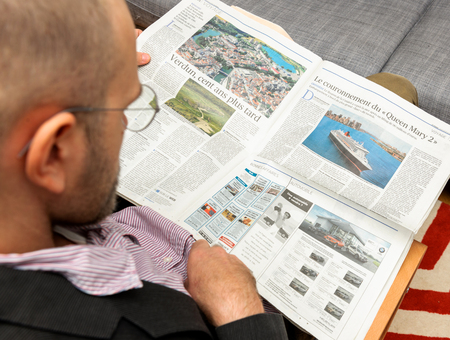newsfeed: PARIS, FRANCE - NOV 12, 2016: Man reading Le Figaro et Vous lifestyle French newspaper - article about Queen Mary 2, the new transatlantic ocean liner