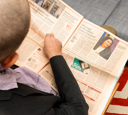 newsfeed: PARIS, FRANCE - NOV 12, 2016: Man reading Le Figaro French Economie newspaper - Marks and Spencer problems in France Editorial