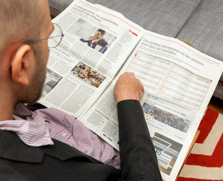 newsfeed: PARIS, FRANCE - NOV 12, 2016: Man reading Le Figaro French newspaper - article about the best company to work for in France