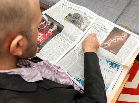 newsfeed: PARIS, FRANCE - NOV 12, 2016: Man reading Le Figaro French newspaper about the Ebola spread and its treatment