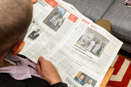 newsfeed: PARIS, FRANCE - NOV 12, 2016: Man reading Le Figaro French newspaper - articles about French industries on USA markets