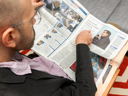 newsfeed: PARIS, FRANCE - NOV 12, 2016: Man reading Le Figaro French newspapper man pointing to Mikheil Saakashvili, portrait while reading magazine