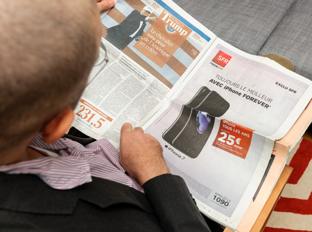 newsfeed: PARIS, FRANCE - NOV 12, 2016: Man reading Le Figaro French newspapper - detailed article about Donald Trump capaign