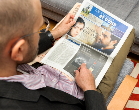 newsfeed: PARIS, FRANCE - NOV 12, 2016: Man reading Le Figaro et Vous lifestyle French newspaper