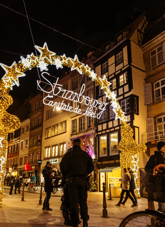 christkindlesmarkt: STRASBOURG, FRANCE - NOV 28, 2015: Police officers surveilling the entrance gate with neon Christmas decorations of the Christmas Market in Strasbourg with high grade security after Paris attacks