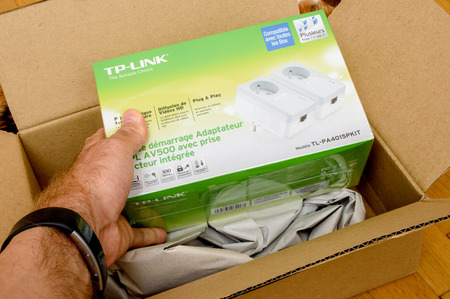 PARIS, FRANCE - SEP 12. 2016: POV of man unpacking of new set of Power-line communication (PLC) made by TP-Link. The communication method that uses electrical wiring to simultaneously carry both data, and Alternating Current (AC) electric power transmissi Редакционное