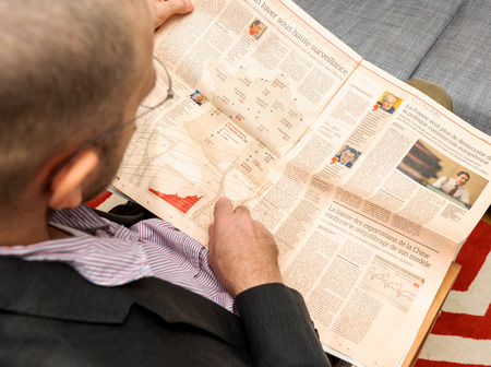 newsfeed: PARIS, FRANCE - NOV 12, 2016: Man reading Le Figaro French Economie newspaper about nuclear plants in France and pointing to their location on map