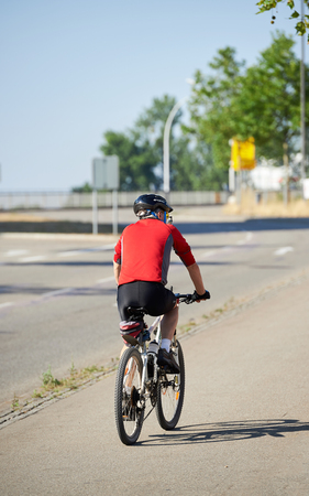 specialised: KEHL, GERMANY - AUG 21, 2015: Rear view of a senior cyclist riding a bike wearing specialised clothes and protection helmet - view from the rear