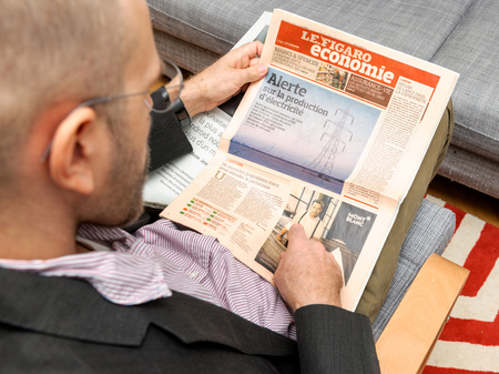 newsfeed: PARIS, FRANCE - NOV 12, 2016: Man reading Le Figaro Economie French newspaper about prices of electricity and current situation on the market Editorial