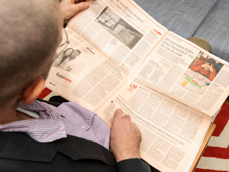 newsfeed: PARIS, FRANCE - NOV 12, 2016: Man reading Le Figaro French Economie newspaper - enjoying article about Google Tax in europe