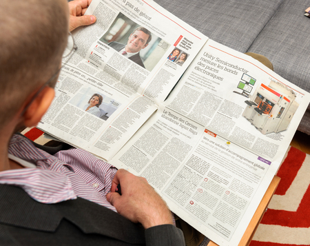 newsfeed: PARIS, FRANCE - NOV 12, 2016: Man reading Le Figaro French newspaper - about Unity Semiconductor business
