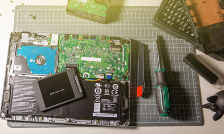 PARIS, FRANCE - DEC 04, 2015: Above view Upgrade of a modern laptop PC computer to the SSD solid state drive disk for faster and better performance for writing media, multimedia archives raid thunderbolt