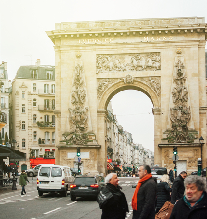 incidental people: PARIS, FRANCE - JAN 23, 2013: Porte Saint-Denis triumphal arch with the entablature bronze inscription LUDOVICO MAGNO, To Louis the Great on a sunny PArisian day Editorial
