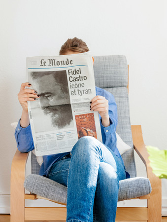 newsfeed: PARIS, FRANCE - NOV 29, 2016: Woman reading Le Monde newspaper with headline and articles about Fidel Castro, Cuban President - dead on November 25, 2016