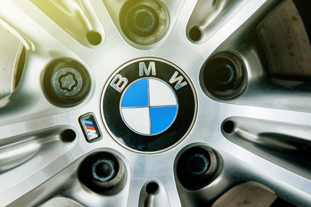 MUNCHEN, GERMANY - APRIL 06, 2015: BMW electric limousine alloy wheel detail with logotype of BMW on it and sun flare