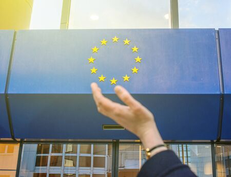 commision: Elegant Woman hand trying to hold the stars of European Union insignia in front of the Council of Europe entrance