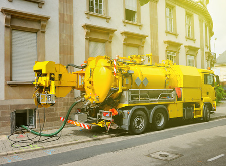 overflows: Working Sewage - sewerage - truck on city street in working process to clean up sewerage overflows, cleaning pipelines and potential pollution issues from an modern building. This type of truck is used for residential septic systems or commercial sewage s