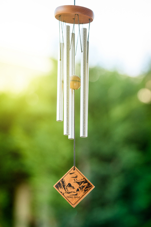 Feng shui chimes with nature in the background with a clear blue sky and defocused tree in the background on a sunny day