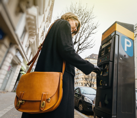 Woman paying for the parking at the teller machine in the city Standard-Bild