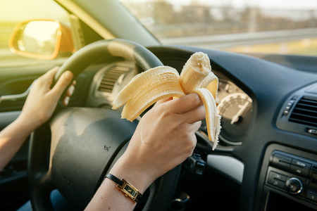 Woman eating a banana while driwing car on highway with 120 kmh Stock Photo