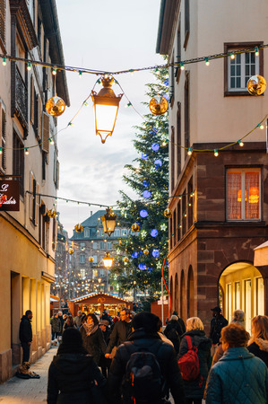 admiring: STRASBOURG, FRANCE - 9 DEC 2016: Majestic Christmas tree seen through building and people visiting the oldest Christmas Market worldwide in central Strasbourg, Alsace Editorial