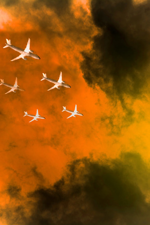 squadron: Squadron of commercial airplanes in flights over orange tempest clouds trying to avoid collision Stock Photo