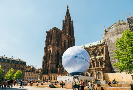 STRASBOURG, FRANCE - MAY 4, 2016: Cathedral Notre-Dame and urban pavilion in central square installed to promote the candidacy of France for the organisation of the World Fair 2025