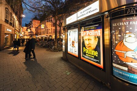 STRASBOURG, FRANCE - DEC 06, 2015: Press kiosk with Vladimir Putin face on he Le Point magazin and headline: Putin is our friend Editorial