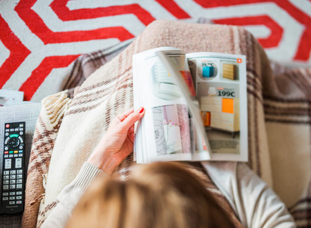 PARIS, FRANCE - AUGUST 24, 2014: View from above of woman browsing the latest IKEA Catalogue before buying furniture for her new house. The catalogue is published annually by the Swedish home furnishing retailer