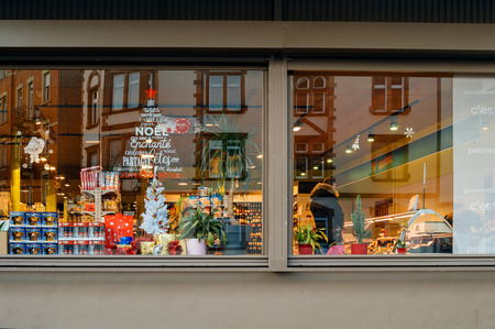 STRASBOURG, FRANCE - DEC 1, 2016:  Carrefour supermarket at the evening with Christmas tree sticker on the windows and customers buying diverse food and non-food products. Carrefour is the largest chain of stores in France