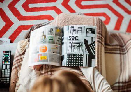 PARIS, FRANCE - AUGUST 24, 2014: View from above of woman reading IKEA Catalogue before buying chairs for her new house. The catalogue is published annually by the Swedish home furnishing retailer