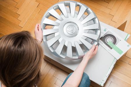 buen trato: PARIS, FRANCIA - 7 DE DICIEMBRE, 2016: Mujer que sostiene unboxing desembalaje moderno centro cubre los neumáticos de invierno realizados por Skoda Auto - buen reparto de las compras en línea de internet Editorial