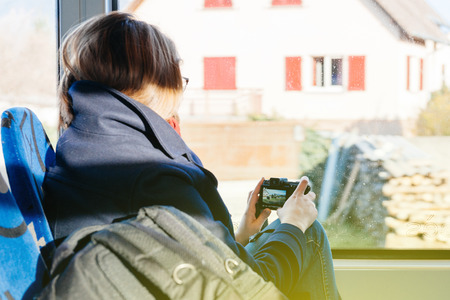 vacance: Woman travel in tramway taking photographs and motion video through the window in France, Mulhouse, Alsace