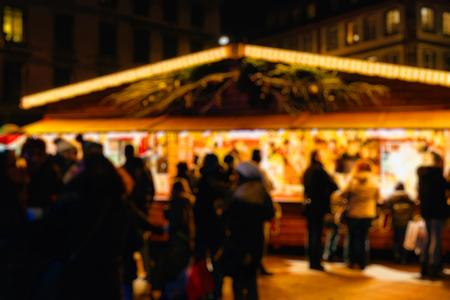 vin chaud: clients Defocused buvant du vin chaud à l'étal du marché traditionnel tout en visitant le plus ancien marché de Noël à travers le monde dans le centre de Strasbourg, Alsace Banque d'images