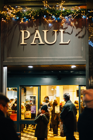 patisserie: STRASBOURG, FRANCE - DEC 20, 2016: Paul Boulangerie Et Patisserie cafe with open doors and women on bike waiting for her friend. Paul is a French chain of bakerycafe restaurants established in 1889 in the city of Croix, in Northern France