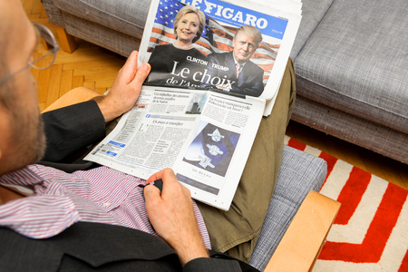 newsfeed: PARIS, FRANCE - NOV 12, 2016: Curious man reading Le Figaro French newspaper with Hillary Clinton and Donald Trump after Trump has won the elections