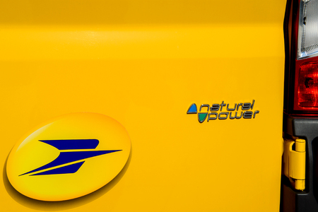 almost all: STRASBOURG, FRANCE - JUN 24, 2016: La Poste logotype on the electric vehicle with the badge Natural Power. Almost all vehicles of postal services in France are environmentally friendly
