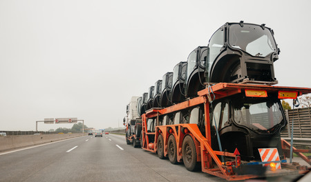 hauling tractor: Big truck with flatbed trailer hauling tractor cabines on german autobahn