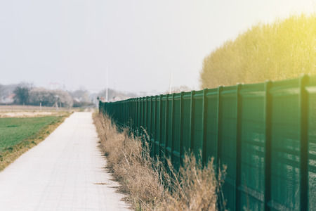 Perspective view of green matallic fence in rural environment similar to prison