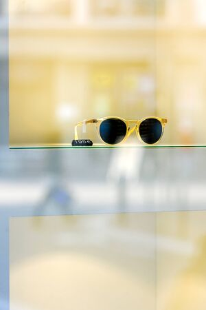 fashion sunglasses: Trendy fashion sunglasses in window store with price tag on yellow background