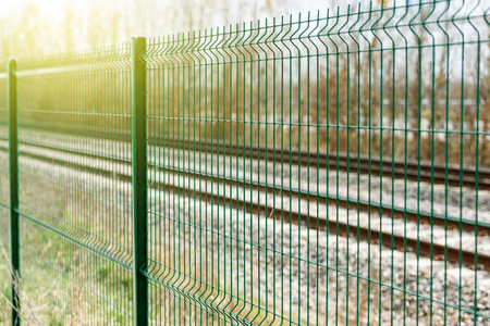 Green matallic fence in rural environment similar to a prison