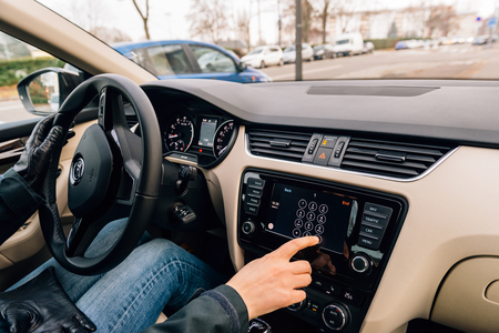 enables: PARIS, FRANCE - DEC 13, 2016: Woman dialing number on the Apple CarPlay main screen in modern car dashboard. CarPlay is an Apple standard that enables a car radio or head unit to be a display and controller for an iPhone. It is available on all iPhone 5 a