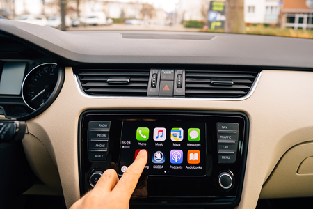 radio unit: PARIS, FRANCE - DEC 13, 2016: Man pressing Now Playing button on the Apple CarPlay main screen in modern car dashboard. CarPlay is an Apple standard that enables a car radio or head unit to be a display and controller for an iPhone. It is available on all