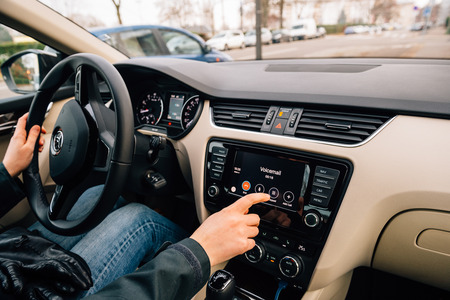 enables: PARIS, FRANCE - DEC 13, 2016: Woman dialing Voicemail on the Apple CarPlay main screen in modern car dashboard. CarPlay is an Apple standard that enables a car radio or head unit to be a display and controller for an iPhone. It is available on all iPhone  Editorial