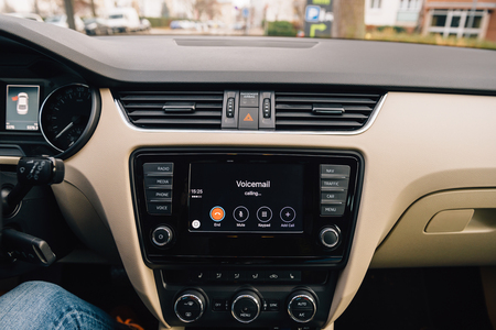 enables: PARIS, FRANCE - DEC 13, 2016: Apple CarPlay main screen in modern car dashboard calling Voicemail. CarPlay is an Apple standard that enables a car radio or head unit to be a display and controller for an iPhone. It is available on all iPhone 5 and later w