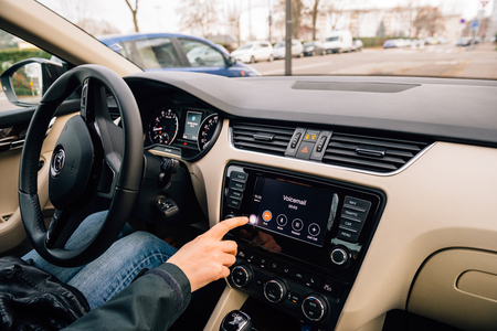 radio unit: PARIS, FRANCE - DEC 13, 2016: Woman pressing Home screen on the Apple CarPlay main screen in modern car dashboard. CarPlay is an Apple standard that enables a car radio or head unit to be a display and controller for an iPhone. It is available on all iPho